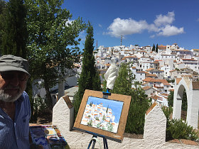Painter with his painting of a white andalusian village